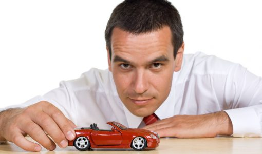 Businessman playing with his dream car - isolated